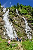 Several persons standing at waterfall Cascata Nardis, Val Genova, Adamello-Presanella Group, Trentino, Italy
