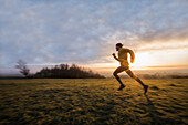 Young man running over a meadow during sunrise, Allgaeu, Bavaria, Germany