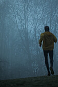 Young man running over a meadow on a foggy autumn day, Allgaeu, Bavaria, Germany