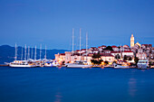 Motor sailing cruise ship M/S Panorama (Variety Cruises) and other yachts at pier with Korcula Old Town and St. Mark's Cathedral at dusk, Korcula, Dubrovnik-Neretva, Croatia