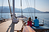 Couple on deck of motor sailing cruise ship M/S Panorama (Variety Cruises) on approach to harbor with mountain backdrop, near Bar, Montenegro