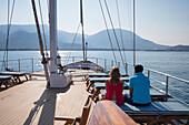 Paar an Deck von Motorsegler Kreuzfahrtschiff M/S Panorama (Variety Cruises) bei der Einfahrt in den Hafen vor Bergkulisse, nahe Bar, Montenegro