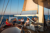 Passengers relax at outside bar at aft of motor sailing cruise ship M/S Panorama (Variety Cruises) at sunset, Adriatic Sea, near Albania
