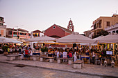 People enjoy dinner at outdoor seating of restaurant on main square at sunset, Gaios, Paxos, Ionian Islands, Greece