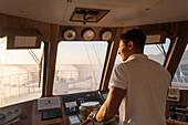 Helmsman on bridge of motor sailing cruise ship M/S Panorama (Variety Cruises) during choppy seas, Adriatic Sea, near Albania