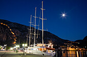 Motor sailing cruise ship M/S Panorama (Variety Cruises) at pier with moon and illuminated Sveti Ivan fortress at night, Kotor, Montenegro