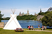 Canada, Ontario Province, Ottawa, Victoria Island, Aboriginal Experiences, teepee and the Parliament of Canada in the background