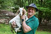 Nature guide holds young goat, near Mespelbrunn, Raeuberland, Spessart-Mainland, Bavaria, Germany