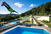 Young man jumps from 5 meter diving tower into swimming pool at Freibad Terrassenbad Frammersbach, Frammersbach, Spessart-Mainland, Bavaria, Germany