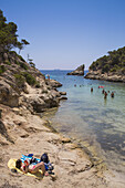 People relax on rocks at Cala Portals Vells bay, Portals Vells, Mallorca, Balearic Islands, Spain