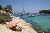 People on rocks relax under sun umbrella with yachts and sailboats at anchor in Cala Portals Vells bay, Portals Vells, Mallorca, Balearic Islands, Spain