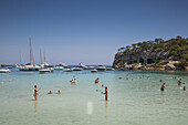 People swim, play and relax in water at beach in Cala Portals Vells bay, Portals Vells, Mallorca, Balearic Islands, Spain