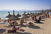 People relax under thatched umbrellas at Playa s'Arenal beach, s'Arenal, near Palma, Mallorca, Balearic Islands, Spain