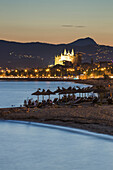 Silhouettes of people and thatched umbrellas at Nassau Beach Club with illuminated La Seu Palma Cathedral in distance at dusk, Palma, Mallorca, Balearic Islands, Spain