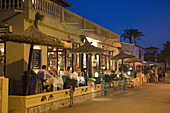 People sit outside and enjoy dinner at Sa Xarxa restaurant on beach promenade at dusk, Colonia de Sant Pere, Mallorca, Balearic Islands, Spain