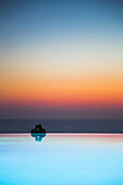 Couple at edge of infinity pool at Jumeirah Port Soller Hotel & Spa at dusk, Port Soller, Mallorca, Balearic Islands, Spain