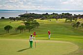 Golfers on green of hole 12 at Club de Golf Alcanada with Faro de Alcanada lighthouse in distance, near Port d'Alcudia, Mallorca, Balearic Islands, Spain