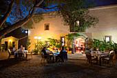 People enjoy outdoor dinner on patio of Finca Predio Son Serra Hotel at dusk, near Muro, Mallorca, Balearic Islands, Spain