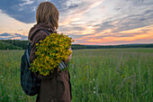 Caucasian woman holding bouquet of flowers in field at sunset