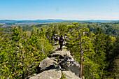 Caucasian man walking on mountain rock admiring scenic view