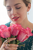 Caucasian woman smelling pink roses