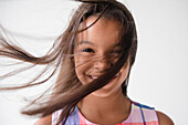 Wind blowing hair of smiling Mixed Race girl