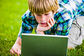 Caucasian boy kneeling in grass using laptop