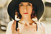 Glamorous Caucasian woman holding hat