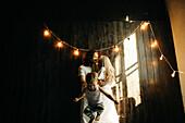 Caucasian couple hugging near boy under string lights