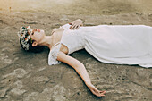 Caucasian bride laying on beach