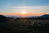 Camping tent in barren field at sunset