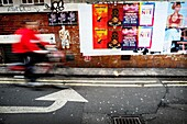 Street scene showing a wall with different advertising posters, unrecognizable man riding a bicycle and left turn arrow sign on the pavement. London, England