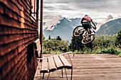 Portrait junger Mountainbiker, Mountainbike, Sprung,  Hütte, Brandnertal, Vorarlberg, Österreich