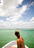 A young woman in a bikini sits in the bow of a white boat as it moves through teal-green water of the Sian Ka'an Preserve.