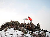 A young woman in an orange jacker and gray pants reaches into a mailbox perched among rocks at the top of a Mailbox Peak in the Cascade Mountains.