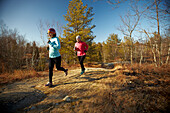 Two young women  cold weather trail running in the Middlesex Fells in Medford, MA.