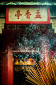 Smoke rising from a large bundle of burning incense sticks at a temple.
