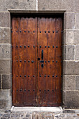 Sixteenth century brown wooden door, with iron fastenings, set in stone doorway, Las Palmas Gran Canaria, Canary Islands, Spain