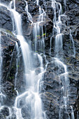 Detail of water cascading down dark rock on Bridalveil Falls in Keystone Canyon, South, central Alaska, Valdez, Alaska, United States of America