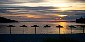 Silhouette of umbrellas on the beach at sunset on a greek island along the Aegean sea, Panormos, Thessalia Sterea Ellada, Greece