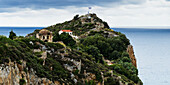 House and old building with greek flag on a rocky promontory along the Aegean Sea, Skiathos, Greece