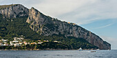 Tall, rugged cliffs along the island of Capri and the town of Capri, Capri, Campania, Italy