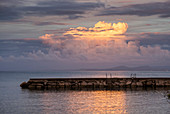 A stone pier out in the tranquil water reflecting the glowing clouds at sunset over the mediterranean, Lacco Ameno, Ischia, Naples, Campania, Italy