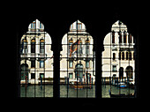 View of a canal through three decorative windows in a row, Venice, Italy
