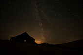 Night sky glowing over silhouette of a barn with a peaked roofline, Palouse, Washington, United States of America