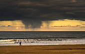 Silhouette of a person and dog walking on the beach at the water's edge under storm clouds with rain streaks and a sunset sky in the distance over the ocean, South Shields, Tyne and Wear, England