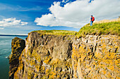 Hiker looking out over ocean, Cape Split along the Bay of Fundy, Nova Scotia, Canada