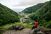 Young woman enjoying the view in Faial da Terra, Sao Miguel, Azores, Portugal
