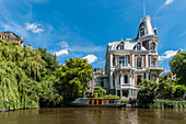 view to canal boats and houses along the Museumsbrug in Amsterdam, Netherlands
