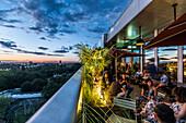 Menschen auf der Terrasse des 25hours Hotel mit Blick auf Zoologischen Garten, Berlin, Deutschland